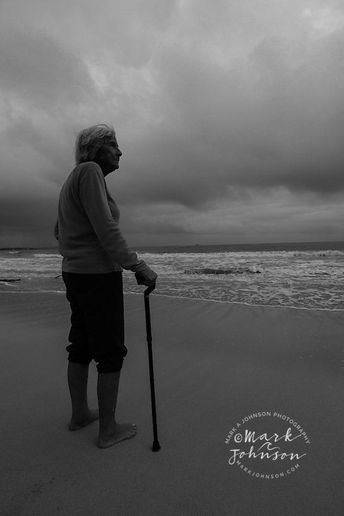 Senior woman on beach under stormy skies, holding cane
