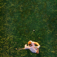 Male golfer viewed from above taking a driving swing.