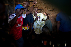 Men spend the afternoon drinking and dancing in a small pub that makes and sells illegal moonshine in Mathare, one of the poorest slums in Nairobi.  Running water and electricity are scarce and trash and human waste fills the streets.  Many people have no jobs and those who do work can earn less than one dollar a day.