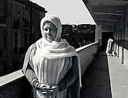 Cairo school headmistress and hadji on the balcony of her school; janitor sweeping beyond her.  The headmistress wears a peaceful, mellow expression, as she has just returned from Mecca.  Her white scarf and drapery indicate this, though in the bright sunlight she must be very hot.  At the other end of the balcony, a subordinate, female servant sweeps the floor, her back turned to us.