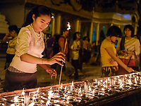 YANGON, MYANMAR - CIRCA DECEMBER 2017: Woman lighting candles at the Shwedagon Pagoda in Yangon at night.