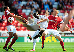 Bristol City's Albert Adomah tries squeeze between Barnsley's Scott Golbourne and Barnsley's Bobby Hassell  - Photo mandatory by-line: Joe Meredith/Josephmeredith.com  - Tel: Mobile:07966 386802 01/09/2012 - Barnsley v Bristol City - SPORT - FOOTBALL - Championship -  Barnsley  - Oakwell Stadium -