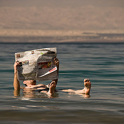 Man reading a newspaper while floating on the Dead sea, Jordan, Asia.