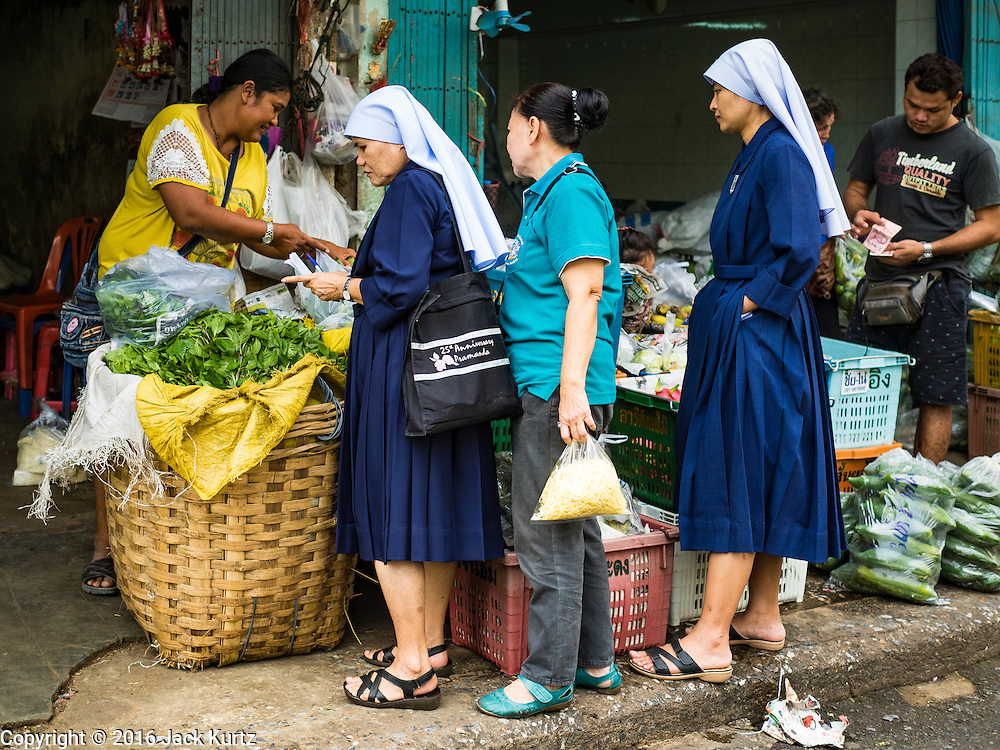 "11 AUGUST 2016 - BANGKOK, THAILAND:  Catholic nuns shop for vegetables for their convent in Pak Khlong Talat in Bangkok. Pak Khlong Talat (literally ""the market at the mouth of the canal"") is the best known flower market in Thailand. It is the largest flower market in Bangkok. Most of the shop owners in the market sell wholesale to florist shops in Bangkok or to vendors who sell flower garlands, lotus buds and other floral supplies at the entrances to temples throughout Bangkok. There is also a fruit and produce market which specializes in fresh vegetables and fruit on the site. It is one of Bangkok's busiest markets and has become a popular tourist attraction.        PHOTO BY JACK KURTZ"