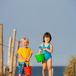A young sister and brother (ages 2 and 4) head to the beach at the Cape Cod National Seashore in Truro, Massachusetts.  Head of the Meadow Beach.