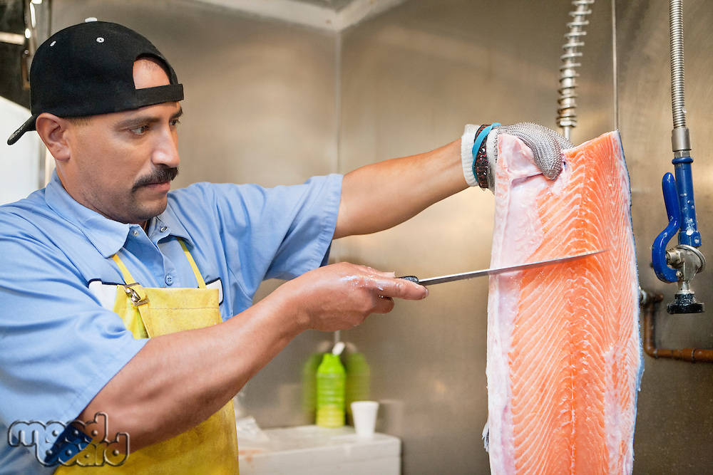 Mature fishmonger slicing salmon fish