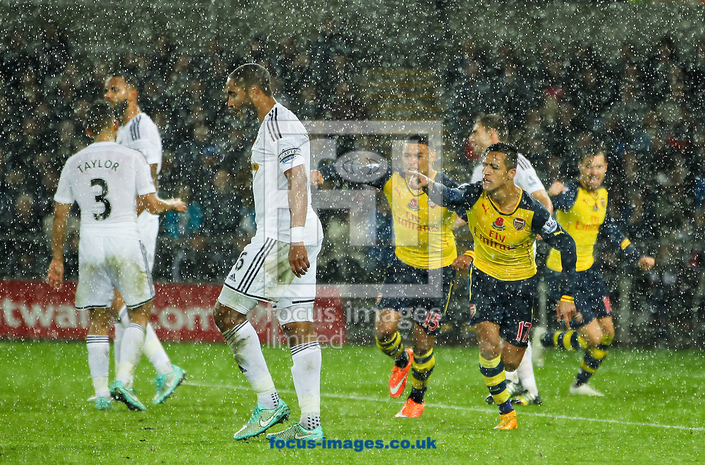 Alexis S&aacute;nchez (2nd right) of Arsenal celebrates scoring his sides first goal during the Barclays Premier League match at the Liberty Stadium, Swansea<br /> Picture by Tom Smith/Focus Images Ltd 07545141164<br /> 09/11/2014