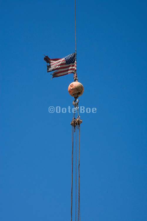 crane cables with an American flag against a blue sky