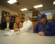 Oxford High's Jon O. Fisher signs to play football at Louisiana-Monroe as his parents Jon Fisher and Elizabeth Fisher, along with Oxford High coach Johnny Hill, look on Wednesday, February 3, 2010 in Oxford, Miss.