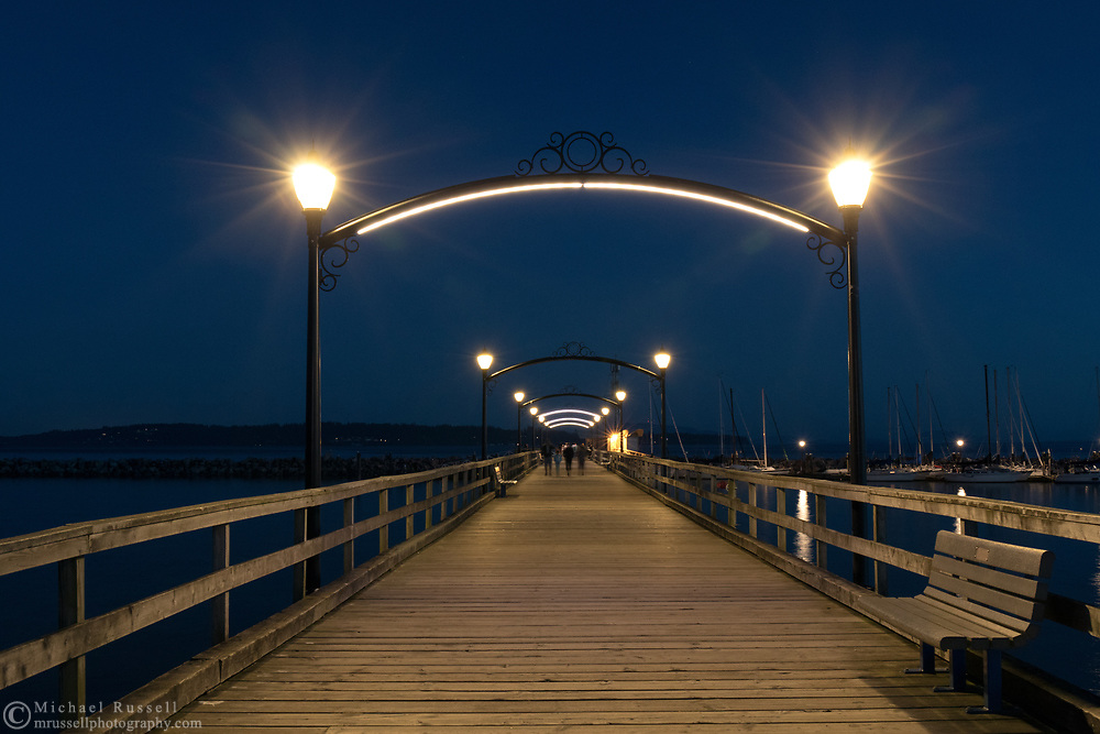 An evening walk on the White Rock Pier towards the marina at the far end.  Photographed in White Rock, British Columbia, Canada.