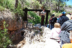 A National Park Service guide speaks to a group of visitors outside the natural entrance to Wind Cave, Wind Cave National Park, South Dakota, United States of America
