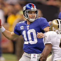 2009 October 18: New York Giants quarterback Eli Manning (10) throws as New Orleans Saints safety Roman Harper (41) pressures during the first quarter at the Louisiana Superdome in New Orleans, Louisiana.