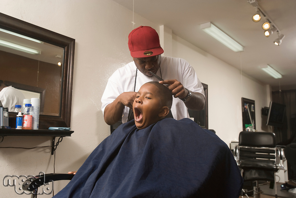 Young boy with hair being shaved in the barbers  while yawning