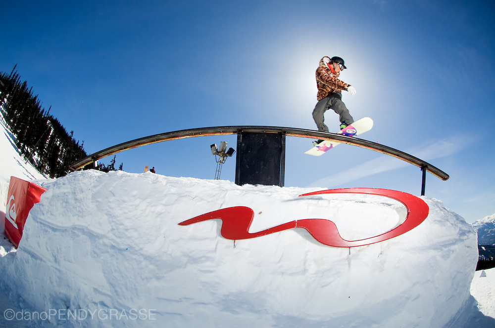 Snowboarder slides rail at Blackcomb park in Whistler, BC.