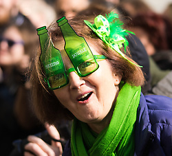 "London, March 13th 2016. The annual St Patrick's Day Parade takes place in the Capital with various groups from the Irish community as well as contingents from other ethnicities taking part in a procession from Green Park to Trafalgar Square.  PICTURED: A woman with ""beer goggles"" watches the procession. ©Paul Davey<br /> FOR LICENCING CONTACT: Paul Davey +44 (0) 7966 016 296 paul@pauldaveycreative.co.uk"