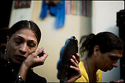 """Sweety and Chabbo (left and right), two  transvestites, respectively of the 27 and 32 years old age, finishes to put  the make up on before a long night in the red lights disctrict. Most of the transvestites people live an extremely marginalized life, for many reasons they create groups and reside in same buildings, where they make a kind of community in alternative to the pakistani society. Evening in Lahore, Pakistan on Tuesday, December 02 2008.....""""Not men nor women"""". Just Hijira, Kusra. Painted lips, Kajal surrounding their eyes and colourful veils..Pakistan is today considered a strongly, foundamentalist as well, islamic country. But under its reputation, above all over the talebans' continuos advancing, stirs a completely extraneous world, a multiethnic mixed society. Transvestites make part of it, despite this would not be admitted by a strict law. Third gender, the Hijira are born as men (often ermaphrodites) or with an ambiguous genital situation, and they have their testicles and penis removed through a - often brutal - surgical operation. The peculiarity is that this operation does not contemplate the reconstruction of a female organ. This is the reason why they are not considered as men nor women, just Hijira. They are often discriminated, persecuted  and taxed with being men prostitutes in the muslim areas. The members of this chast perform dances during celebrations, especially during weddings, since it is anciently believed that an EUNUCO's dance and kiss in the wedding day brings good luck to the couple's fertility...To protect the identities of the recorded subjects names and specific .places are fictionals."""
