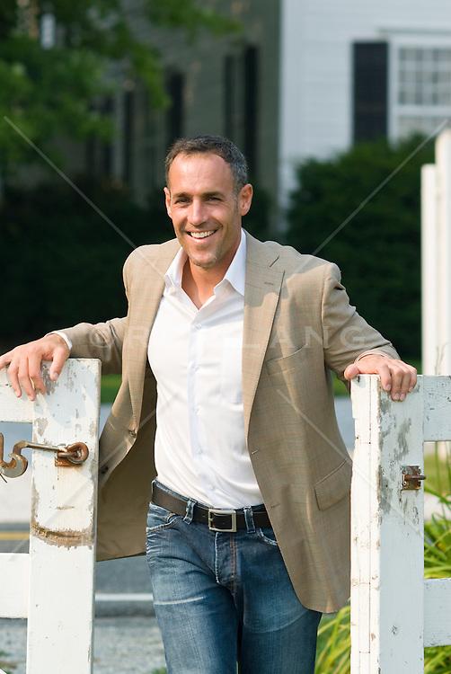 Man in a sports jacket walking through a white gate