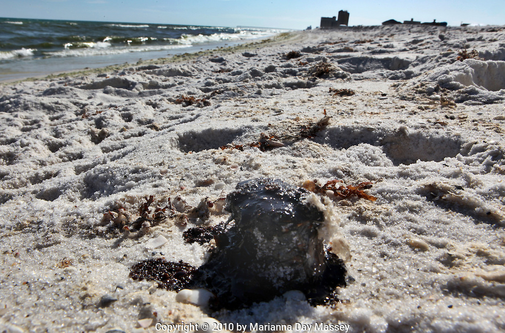 Jul 27, 2010 - Pensacola, Florida, United States - Tar balls on the white sand beaches of Pensacola Tuesday. Waves of gooey tar blobs were washing ashore in growing numbers on the white sand of the Florida Panhandle Tuesday as slicks from the BP spill continue to drift  ashore. The tar balls came ashore after prevailing winds died and were replaced with heavy onshore winds. The tar balls washed up 15 feet at Pensacola Beach, which is already suffering from massive vacation cancellations. BP halted cleanup crews after a tropical storm threat but have reinstated efforts this week..(Credit Image: © Marianna Day Massey/ZUMA Press)