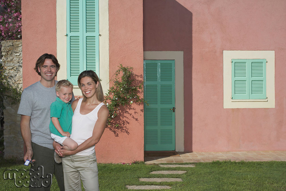 Portrait of family with boy (2-3) in front of house