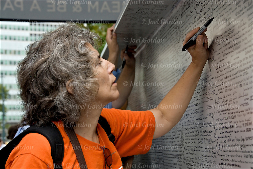 Woman adding her name to steel beams that will be used in the contruction of the National September 11 Memorial Museum on the 7th Anniversary of 9/11 at Battery Park in New York.