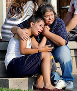 Lisa Kepler, age 18, hugs Pam Wilkins on the steps of Wilkins' home in Tulsa, OK. Kepler's boyfriend and nephew of Wilkins, Jeremy Lake, was shot by Lisa's father, Tulsa Police officer Shannon Kepler outside the house while checking on his daughter.
