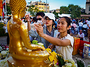01 JANUARY 2019 - BANGKOK, THAILAND:   Women apply gold leaf to a statue of the Buddha at the New Year's merit making ceremony on the plaza in front of City Hall in Bangkok. City Hall traditionally hosts one of the largest New Year merit making ceremonies in Thailand. This year about 160 monks participated in the event.    PHOTO BY JACK KURTZ