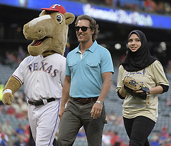 September 13, 2017 - Arlington, TX, USA - Matthew McConaughey, center, escorts Samiya Momhamed-Fawzy, a 17-year-old senior from Sam Houston High School, as she prepares to throw out the ceremonial first pitch as the Texas Rangers play host to the Seattle Mariners at Globe Life Park in Arlington, Texas, on Wednesday, Sept. 13, 2017. (Credit Image: © Max Faulkner/TNS via ZUMA Wire)