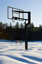 Closed for the season.  A basketball net towers above snow patterns in Swanzey, New Hampshire.