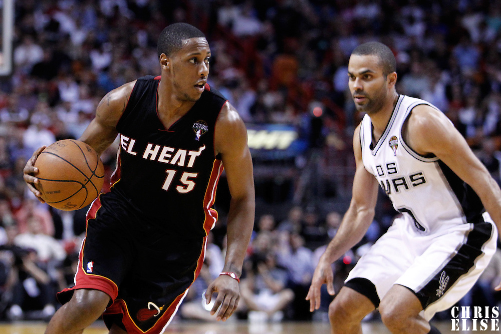 14 March 2011: Miami Heat point guard Mario Chalmers (15) drives past San Antonio Spurs point guard Tony Parker (9) during the Miami Heat 110-80 victory over the San Antonio Spurs at the AmericanAirlines Arena, Miami, Florida, USA.
