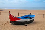 Traditional red white and blue wooden Portuguese fishing boat on the beach of Nazare, Portugal. These boats are on display by the Dry Fish Museum