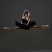 Classical female ballet dancer, Marie Tender,  in a black tutu in a jete jump the photo studio on a black background. Photograph taken in New York City by photographer Rachel Neville.