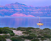 Sailboat at anchor in at Isla San Francisco at dawn with the Mountains of Baja California [Sierra Giganta] in distance.  Sea of Cortez, Mexico.