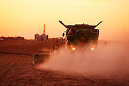 Midwest soybean harvest, dusty combine silhouette at sunset