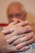 Hands of an elderly gentleman in a counselling session.