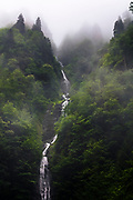 Waterfall falls down in the river high from the mountain
