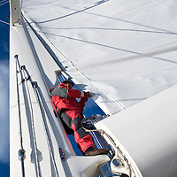 A crew member guides the carbon fiber mainsail as it is hoisted for a voyage across the Atlantic Ocean via the Azores