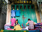 30 MAY 2013 - BANGKOK, THAILAND:   Women set up their stall on a sidewalk in front of a store in Bobae Market in Bangkok. Bobae Market is a 30 year old famous for fashion wholesale and is now very popular with exporters from around the world. Bobae Tower is next to the market and  advertises itself as having 1,300 stalls under one roof and claims to be the largest garment wholesale center in Thailand.   PHOTO BY JACK KURTZ