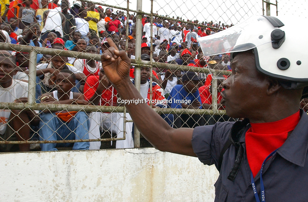 National Police confront unruly fans as they patrol the perimeter of the pitch.