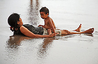 Mother and child cooling off and having fun at the beach in Bali, Indonesia.