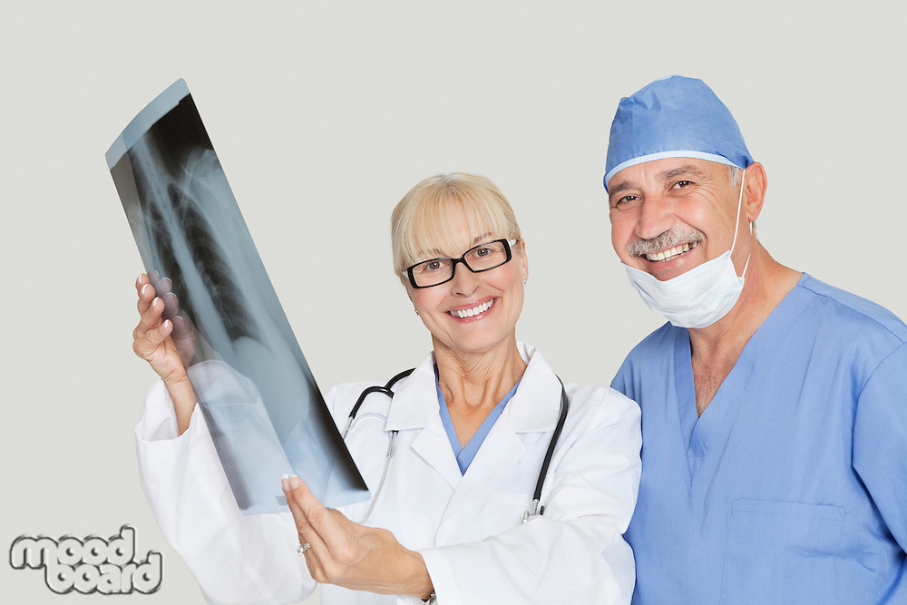 Portrait of happy medical colleagues with radiograph over gray background