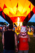 As dusk falls to night, a family with child watches burner flames illuminate a hot air balloon during a balloon glow event, part of the Monroe Balloons and Blues Festival at the Green County fairgrounds in Monroe, Wis., during summer on June 18, 2016. (Photo by Jeff Miller, www.jeffmillerphotography.com)