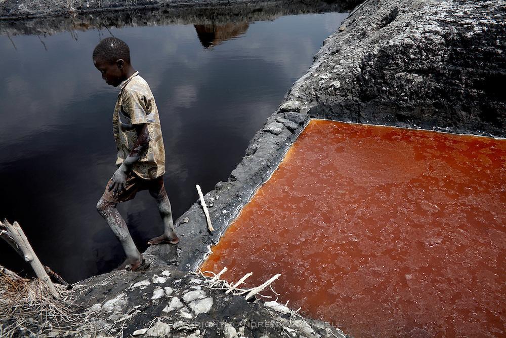 A boy stands between salt pans at Lake Katwe.