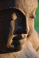 Closeup of the face of a stone Buddha.