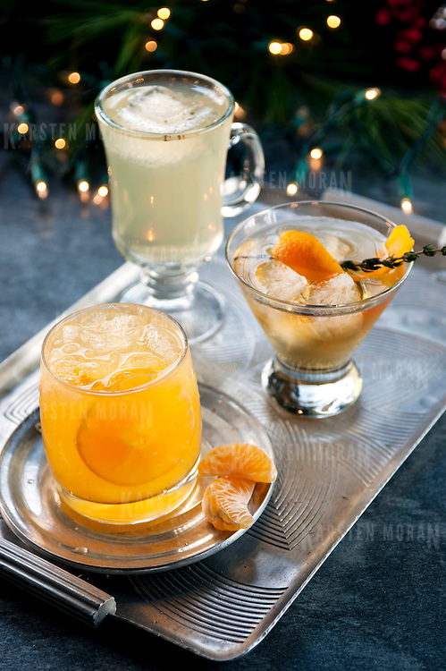 "December 2, 2013 - New York, NY : A selection of holiday cocktails, prepared and styled by Suzanne Lenzer, include, from front to back, the ""Bad Day at Work"" (garnished with clementines), the ""Tabard Cocktail"" (with sprig of Thyme), and the ""Green Tea Punch"" (dusted with grated nutmeg). CREDIT: Karsten Moran for The New York Times"