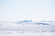 A large farmhouse and barn seem small on the horizon in this winter landscape across the frozen Iowa plains.