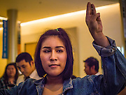 20 NOVEMBER 2014 - BANGKOK, THAILAND: NATCHACAH KONG-UDOM walks through the lobby of the Siam Paragon movie theaters displaying the three fingered salute from the Hunger Games movies. She was one of at least three people arrested by Thai police during the opening the Hunger Games: Mockingjay - Part 1 in Bangkok Thursday. Opponents of the Thai military coup have adapted the three fingered salute used in the Hunger Games series as a sign of their opposition to the coup. In the weeks before the movie opening Thai police arrested several people for using the Hunger Games salute and Thai media reported that one Thai movie theater chain cancelled plans to show the movie at the request of the military government. There were several small protests at theaters showing the movie Thursday.     PHOTO BY JACK KURTZ