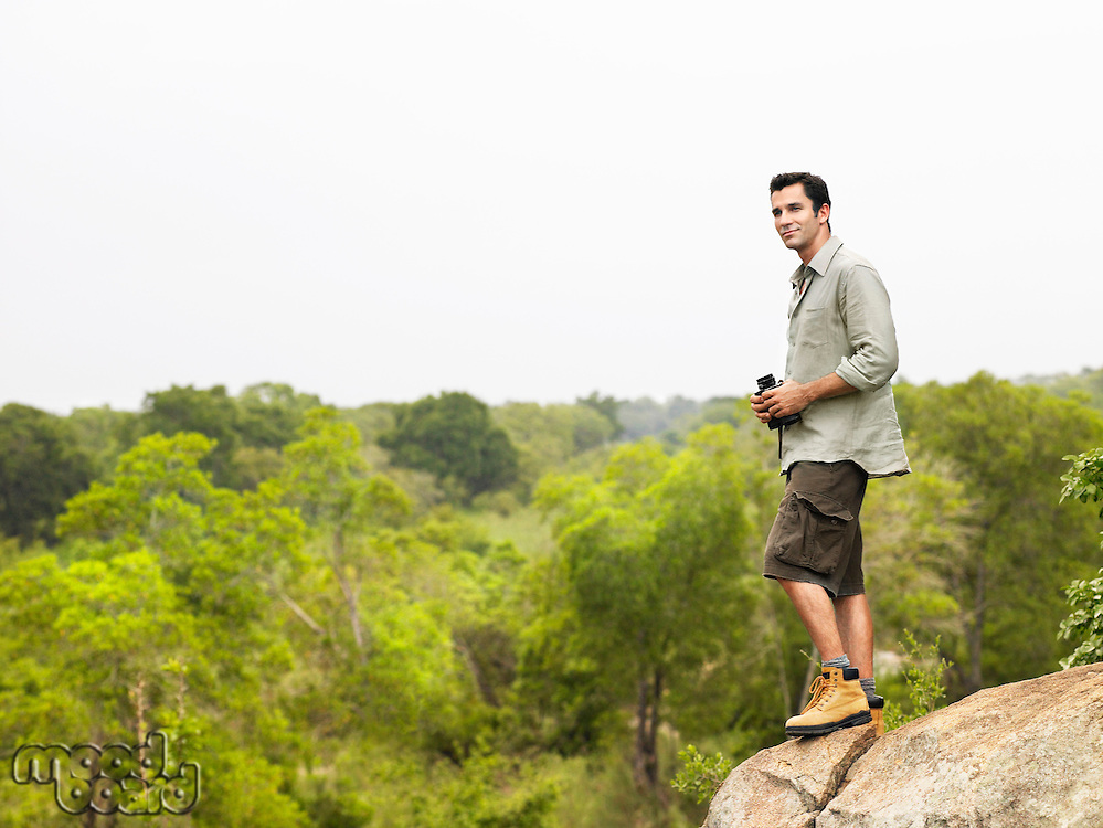 Mid adult man standing on rock looking at view holding binoculars