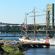 The U.S. Coast Guard Eagle approaches the NH State Pier in Portsmouth Harbor on August 2, 2013, to participate in Sail Portsmouth, hosted by the Piscataqua Maritime Commission. Kittery, ME, the Sarah Long Bridge, and the I-95 Bridge are in the background.