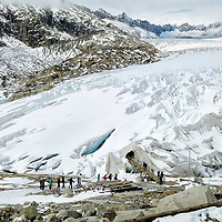 Tourists entering a canvas shelter leading into a tourist attraction cut into the Rhone Glacier. They hope to protect the entry to the glacier against the effects of climate change with the canvas covering. The glacier has receded  1300 m in the last 120 years.