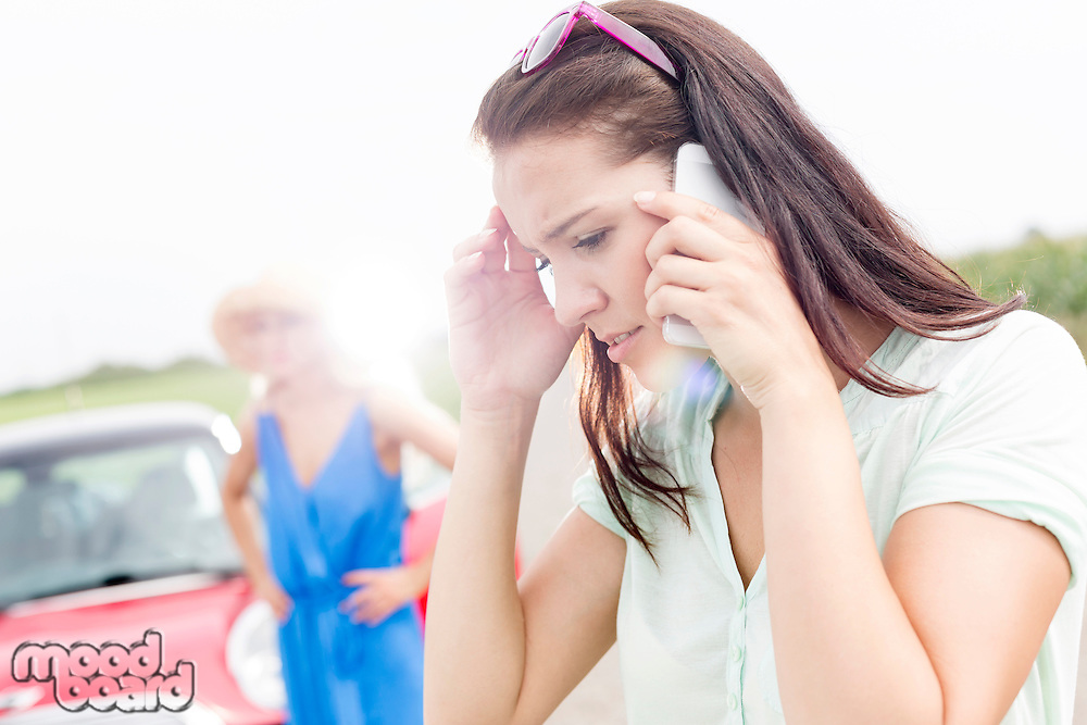 Worried woman using mobile phone while friend standing by broken down car on sunny day